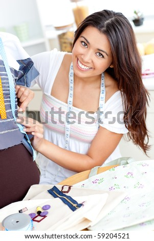 charming asian girl sewing in her bedroom smiling at the camera - stock photo
