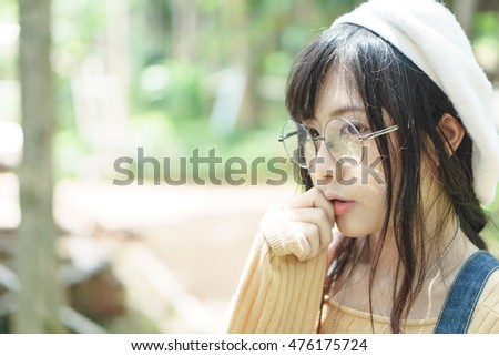 Charming Asian girl wearing jean overalls in the park