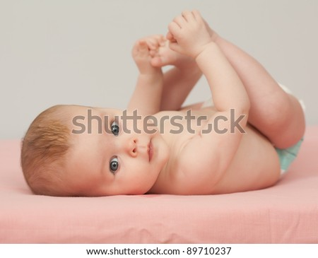 Charming baby. A blue eyed baby lying on back looking at camera - stock photo