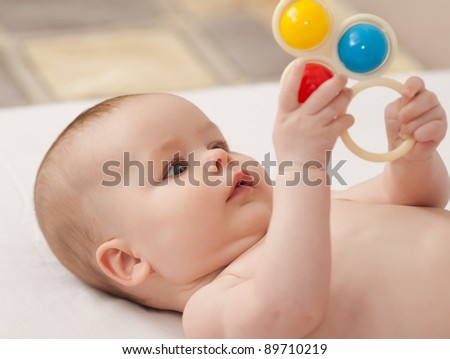 Charming baby. Baby girl playing with toy rattle lying on back - stock photo