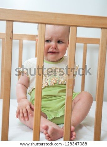 Charming baby indoor. Baby girl in child bed - stock photo
