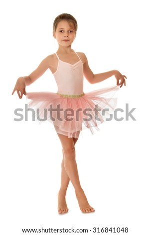 Charming ballerina child of school age in a short pink dance dress , standing on toes and keeps the edges of the skirt fingers-Isolated on white background