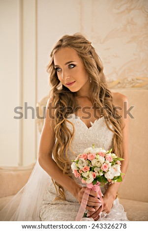 charming beautiful bride holding wedding bouquet in her hands. bride in white dress in a luxury interior of her bright bedrooms. Bride with long beautiful blond hair. bride in veil sitting on the sofa