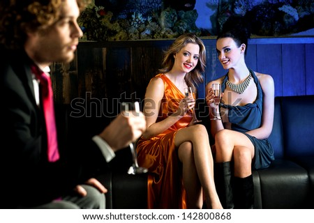 Charming beautiful girls looking at handsome young guy in a bar. - stock photo