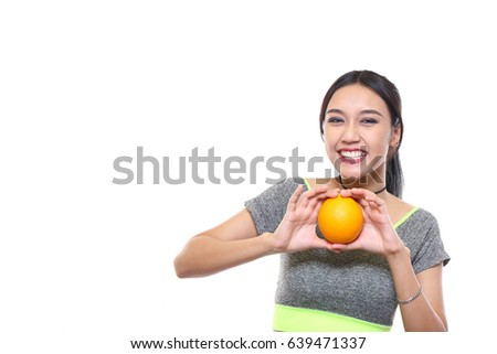 Charming beautiful tan skin sporty Asian woman with exercise suit hand hold orange isolated on white background. Presenting good health and fitness concept.