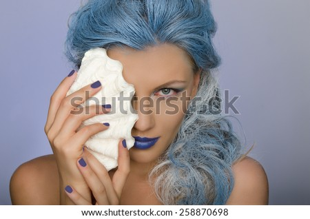 charming  beautiful woman with blue hair and shell of person - stock photo