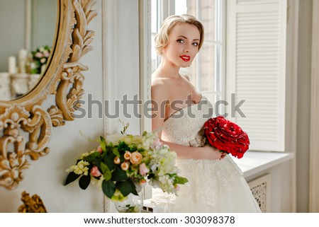 Charming beautiful young blonde girl with red lipstick on my lips, with red roses and white lace dress standing at the window in the interiors of the house