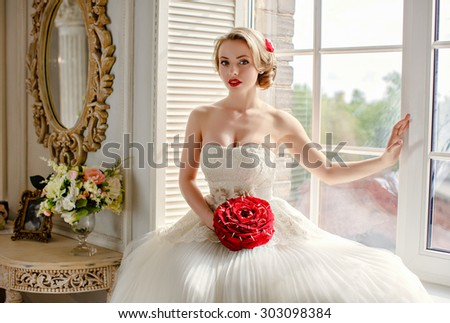 Charming beautiful young blonde girl with red lipstick on my lips, with red roses and white lace dress sits on the window in the interiors of the house