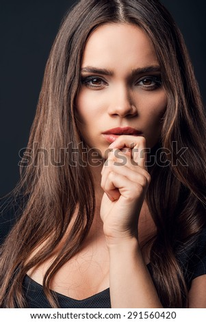 Charming beauty. Beautiful young woman holding hand near her face while standing against black background - stock photo