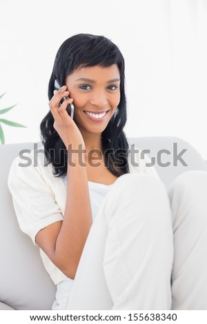 Charming black haired woman in white clothes phone calling in a living room - stock photo