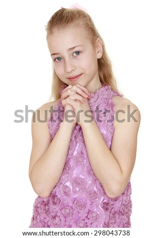 Charming blond Caucasian girl with long hair in pink long dress folded his hands in front of face, close-up-Isolated on white background - stock photo