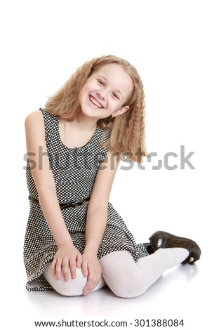 Charming blond girl with short bushy hair sitting on the floor. On the girl wearing a gray silk gown tied with a strap and white tights.-Isolated on white background - stock photo
