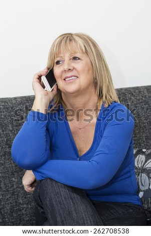 Charming blond haired mature woman sitting on the sofa in the living room and talking by smart phone. - stock photo
