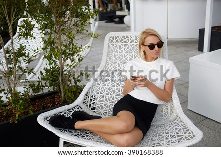 Charming blonde female is looking away, while is sitting in comfortable chair with mobile phone in hands. Hipster girl in fashionable clothes is using cell telephone during rest in modern coffee shop - stock photo