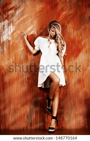 Charming blonde girl in romantic white dress over vivid background. - stock photo