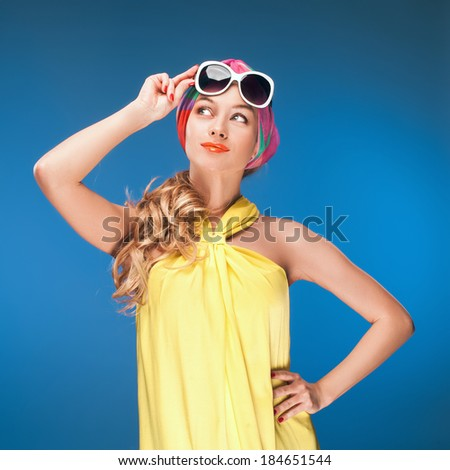 Charming blonde girl in vintage yellow dress and sunglasses over blue background.