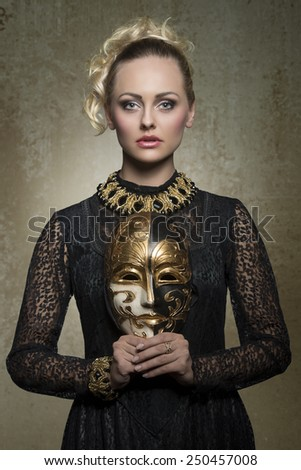 charming blonde girl posing in carnival shoot with antique baroque gothic costume, black lace dress, precious jewellery and theatrical mask in the hands  - stock photo