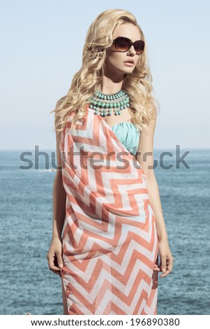 charming blonde girl posing in fashion shoot with summer look. Wearing sunglasses, pareo on bikini and turquoise necklace.  - stock photo