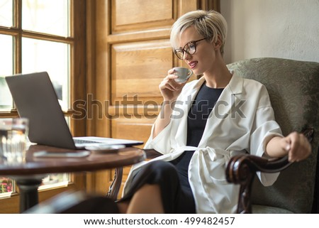 Charming blonde girl with a smile in glasses sits on the armchair at the table in the restaurant. She holds a cup in right hand and looks at the laptop. Woman wears black dress and a white cloak.
