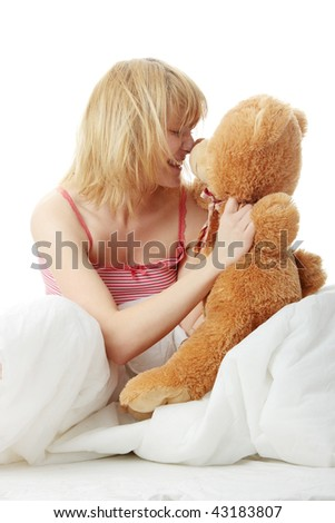 Charming blonde in bed embraces teddy bear isolated