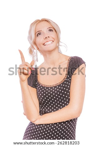 Charming blonde in dark dress shows fingers upwards and smiles, isolated on white background.