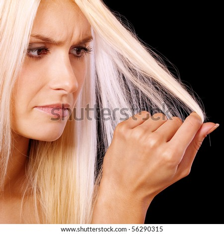 Charming blonde is not happy with fragile hair, it is isolated on black background.