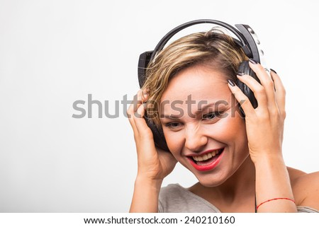 Charming blonde posing on a white background with stereo headphones. Girl holding headphones, listening to music. Headphones, music, advertising headphones. The concept of listening to music. - stock photo