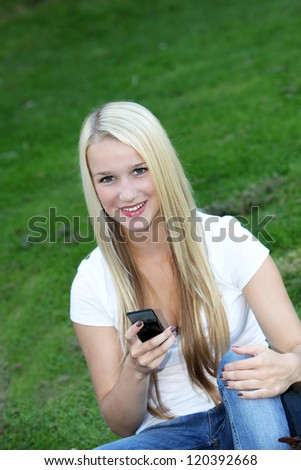 Charming blonde teenaged girl sitting on green grass looking up and smiling at the camera with a mobile phone in her hand - stock photo