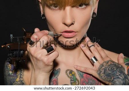 charming blonde with tattoo machine and for them, dark background
