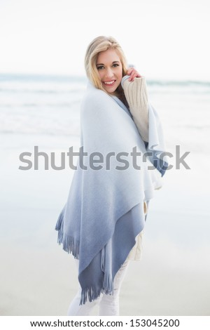 Charming blonde woman covering herself in a blanket on the beach