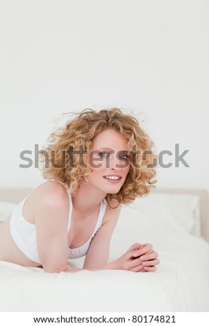 Charming blonde woman relaxing while lying on her bed in her apartment - stock photo