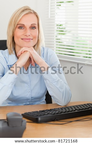 Charming blonde woman with chin on her hands behind a desk in an office - stock photo