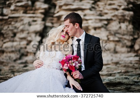 Charming bride and elegant groom on landscapes of mountains and rocks. Gorgeous wedding couple - stock photo