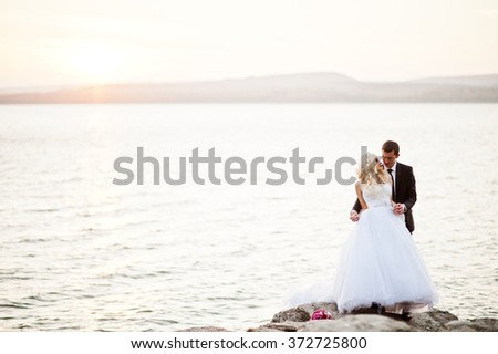 Charming bride and elegant groom on landscapes of mountains and sunset at lake. Gorgeous wedding couple - stock photo