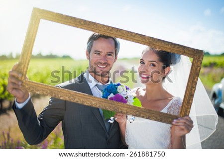 Charming bride and groom posing with a frame for their wedding photos, behind them a lovely country road - stock photo