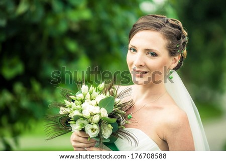 Charming bride walks in the park. - stock photo