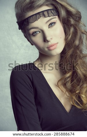 charming brunette female with volume wavy long hair and stylish make-up posing in close-up portrait. Wearing black dress  - stock photo