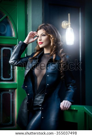 Charming brunette in black leather outfit with green painted door on background. Sexy gorgeous young woman with long curly hair. Portrait of sensual woman with red lips and provocative low-cut neck  - stock photo
