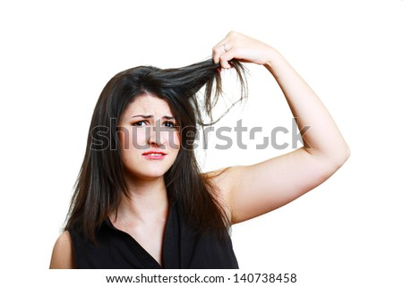 Charming brunette is not happy with fragile hair, isolated on white background. - stock photo
