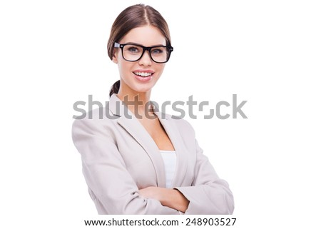 Charming businesswoman. Confident young businesswoman keeping arms crossed and smiling while standing against white background