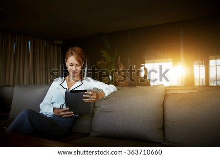 Charming businesswoman reading feminine article in social network via touch pad while waiting for menu in modern coffee shop,female using digital tablet for search information for forthcoming meeting - stock photo