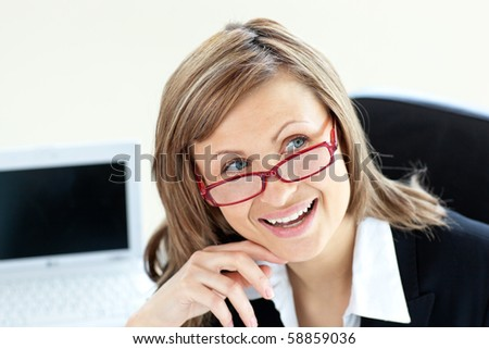 Charming businesswoman sitting on a chair wearing glasses against white background - stock photo