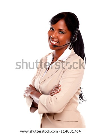 Charming call center employee smiling at you while wearing her headset against white background - stock photo