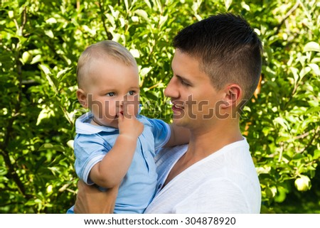 charming caucasian baby boy with father in garden - stock photo