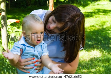 charming caucasian baby boy with mother in garden