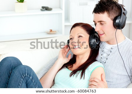 Charming caucasian couple listening to music wearing headphones on the couch at home - stock photo