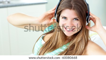 Charming caucasian girl listening to music sitting on a sofa at home