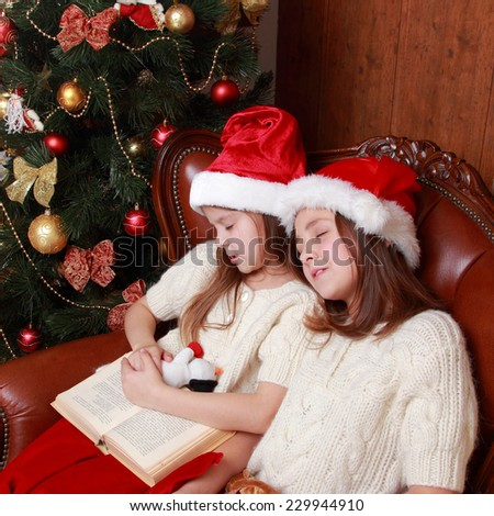 Charming caucasian sisters with red and white Santa's hat sleeping snuggled together on Holiday theme - stock photo