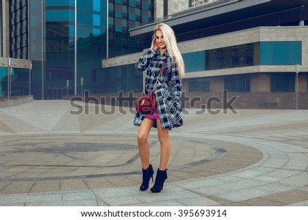 Charming cheerful blonde girl in coat posing outdoors and smiling on the camera. fashion model posing outdoors. fashionable and glamour concept. - stock photo