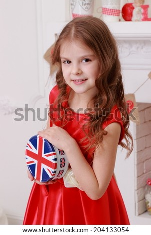 Charming cheerful little girl with beautiful hair in red dress on Valentine's Day